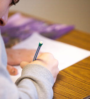 A student writing on a piece of paper with a pencil