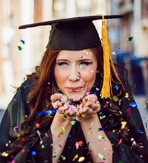 A graduate blowing confetti into the camera